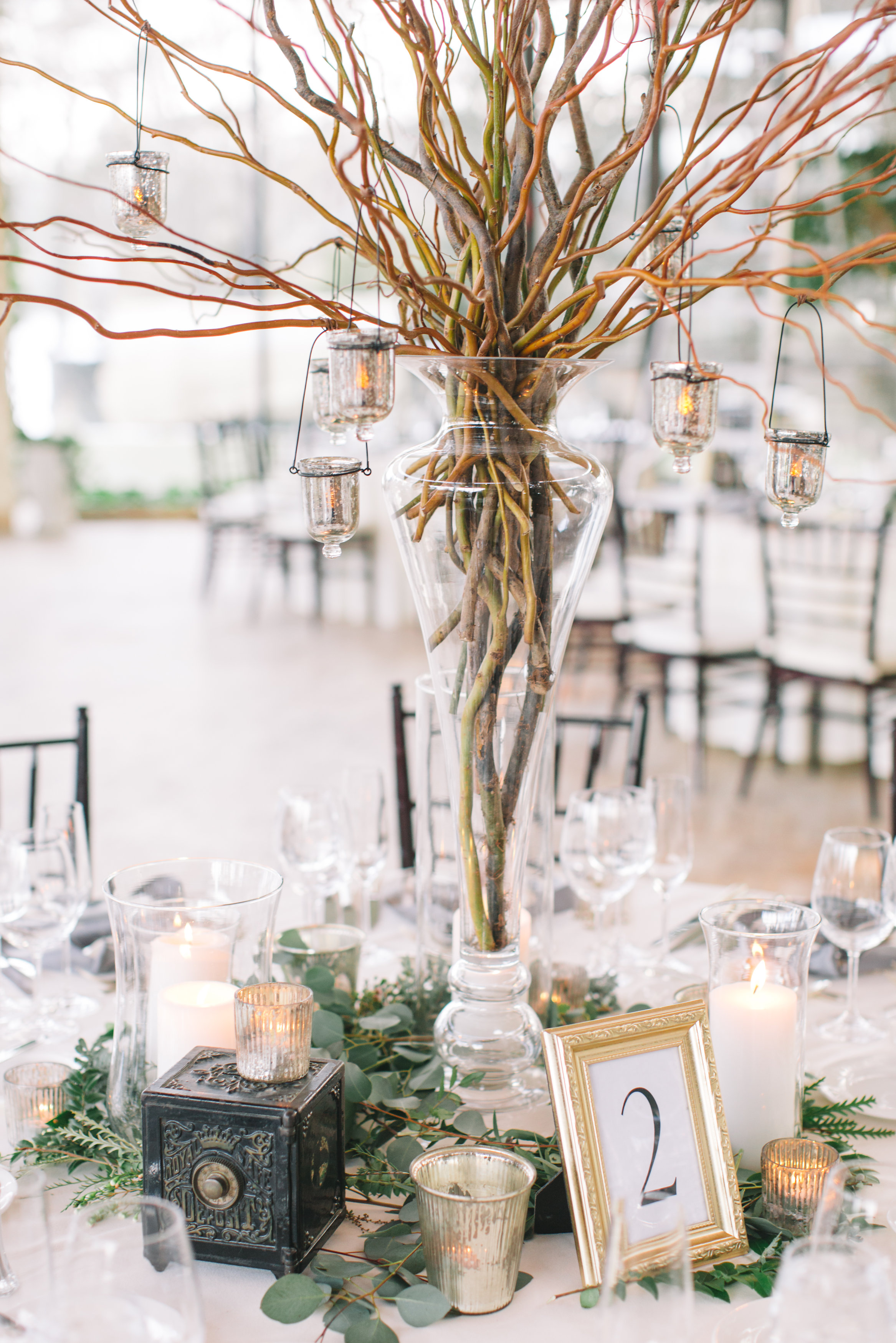 Tall branch centerpiece with hanging votives · allium