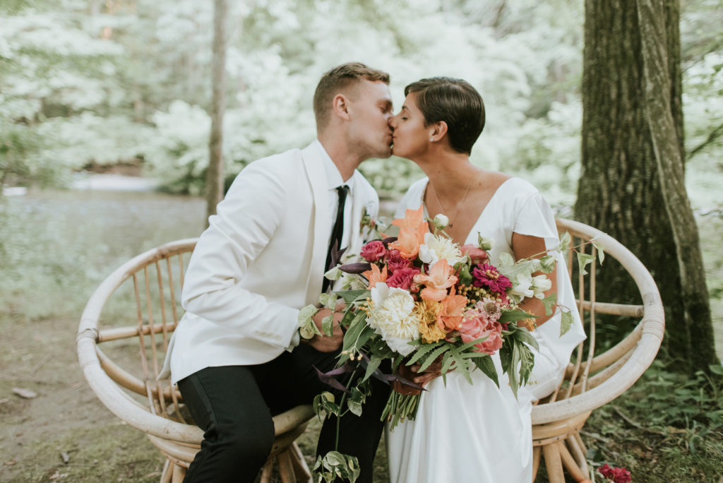 Bride and Groom with Colorful florals and Wooden Chairs