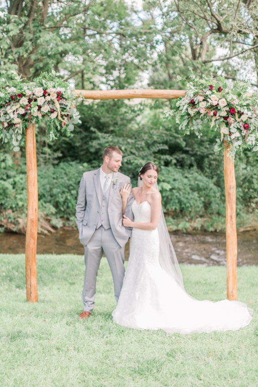 White burgundy blush green bride and groom and arbor