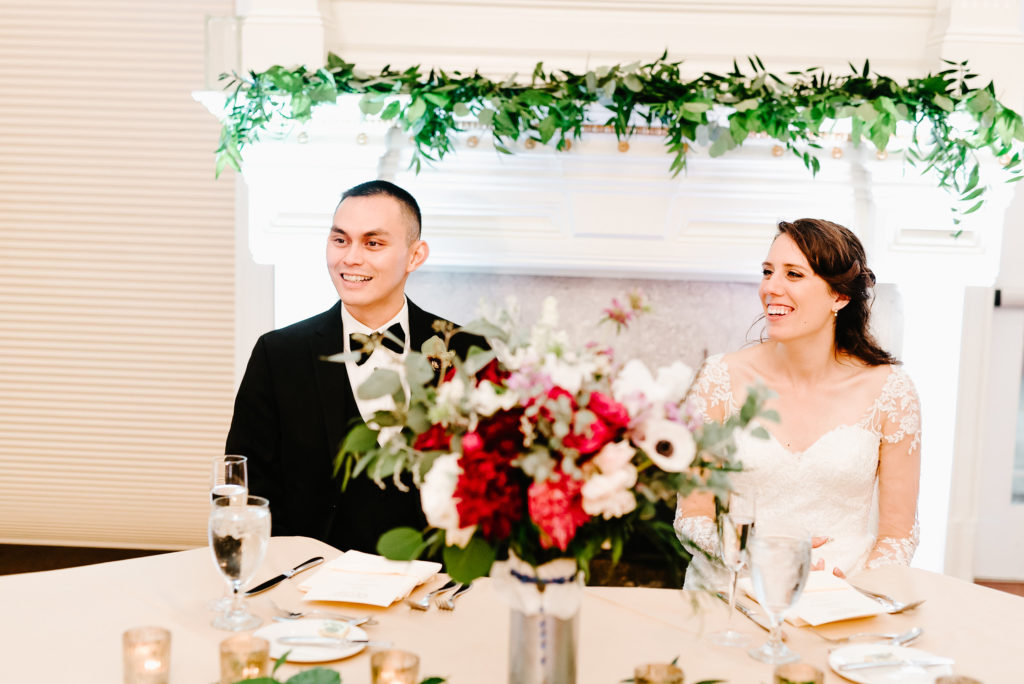 red, purple, lush greenery, stylish, wedding, sweetheart table, greenery mantle