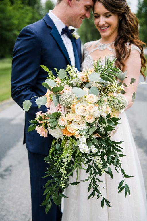 whimsical organic farm wedding, coral, peach, green, blush, roses, tulips, allium, cascade bridal bouquet, bride and groom