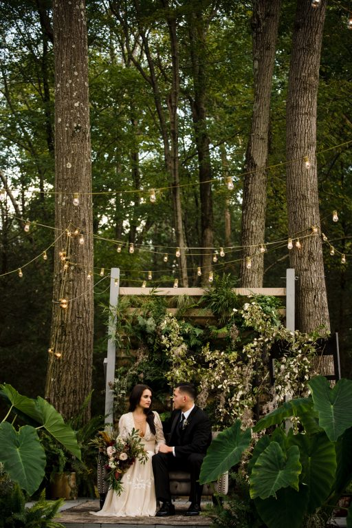 The Originals inspired styled shoot, elopement, microwedding, mysterious, moody, dark color palette, roses, greenery, organic, wild, fall, pinks, purples, yellows, black, grey settee, bride and groom, greenery wall.