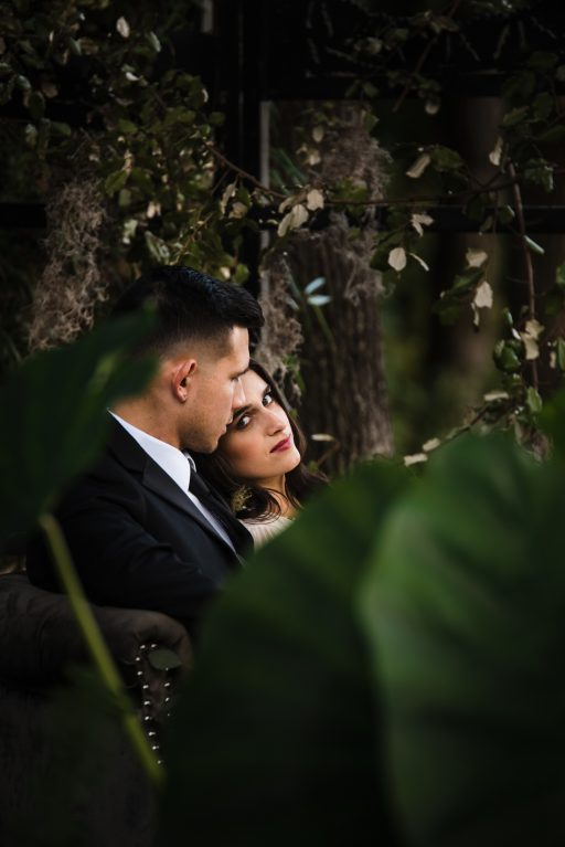 The Originals inspired styled shoot, elopement, microwedding, mysterious, moody, dark color palette, roses, greenery, organic, wild, fall, pinks, purples, yellows, black, grey settee, greenery wall, bride and groom.