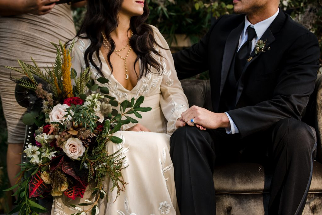 The Originals inspired styled shoot, elopement, microwedding, mysterious, moody, dark color palette, roses, greenery, organic, wild, fall, pinks, purples, yellows, black, grey settee, bride and groom, greenery wall, ceremony.