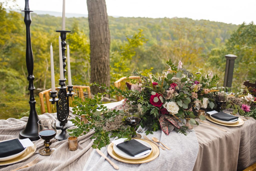 The Originals inspired styled shoot, elopement, microwedding, mysterious, moody, dark color palette, roses, greenery, organic, wild, fall, pinks, purples, yellows, black, long table, floral arrangement, taper candles, candle sticks.