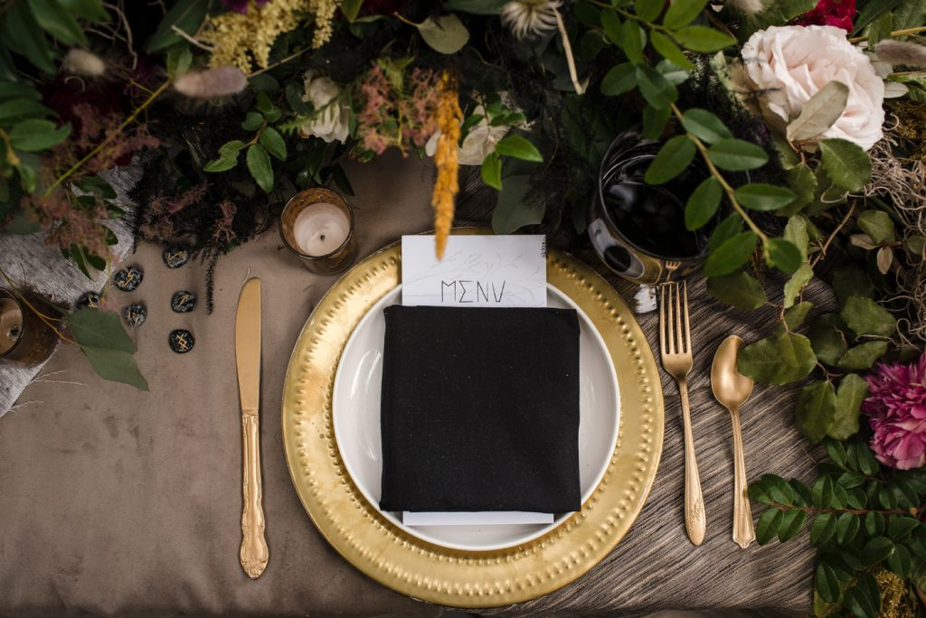 The Originals inspired styled shoot, elopement, microwedding, mysterious, moody, dark color palette, roses, greenery, organic, wild, fall, pinks, purples, yellows, black, long table, floral arrangement, gold flatware, table setting, gold charger.