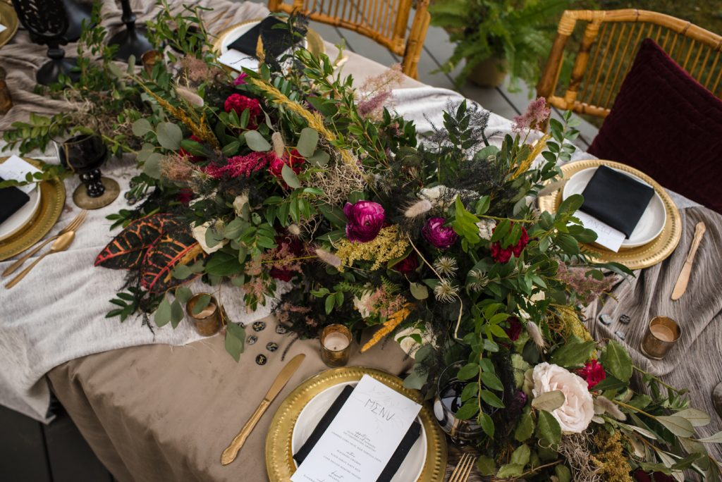 The Originals inspired styled shoot, elopement, microwedding, mysterious, moody, dark color palette, roses, greenery, organic, wild, fall, pinks, purples, yellows, black, long table, floral arrangement, gold flatware, table setting, gold charger, long arrangement.