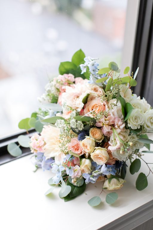 Subtle fall wedding, classic, elegant, peach, blues, hint of orange, blue thistle, roses, eucalyptus, delphinium, bridal bouquet.