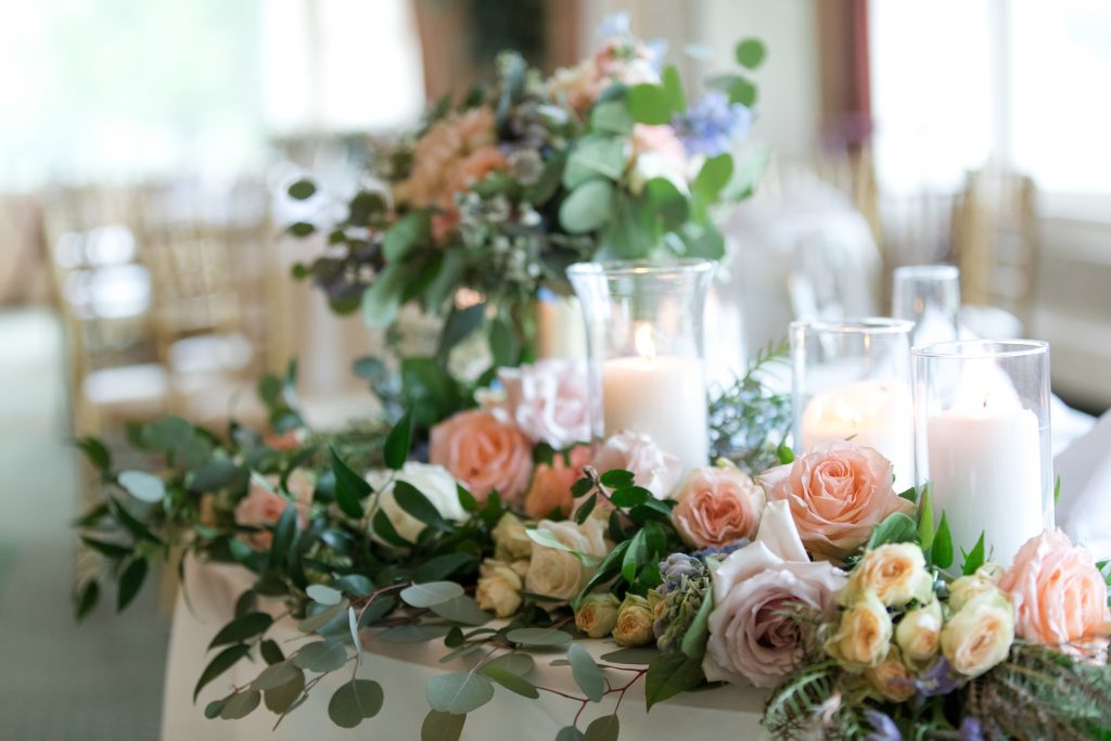 Subtle fall wedding, classic, elegant, peach, blues, hint of orange, blue thistle, roses, eucalyptus, delphinium, sweetheart table, floral swag, pillar candles.