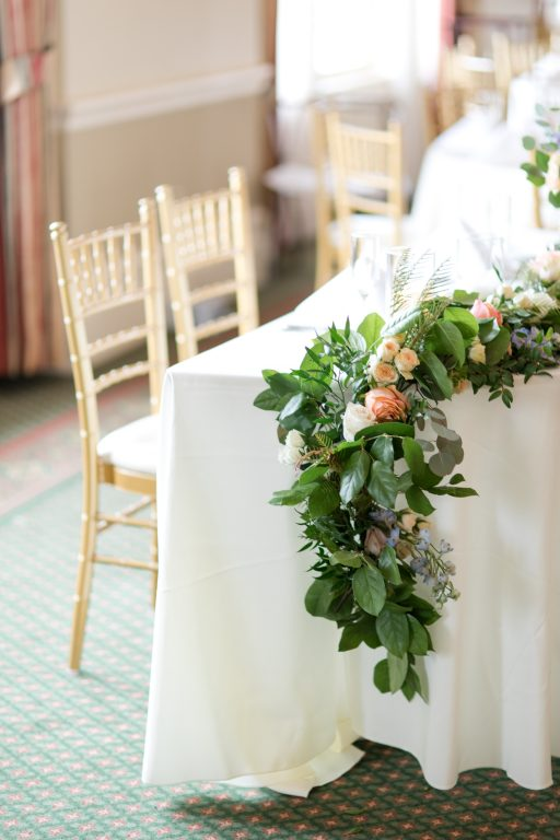 Subtle fall wedding, classic, elegant, peach, blues, hint of orange, blue thistle, roses, eucalyptus, delphinium, sweetheart table, floral swag.