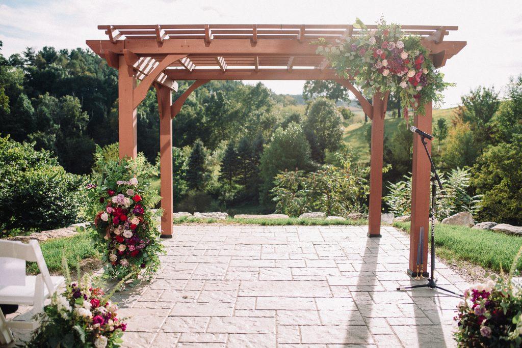 Whimsical, fall, autumn, jewel tones, gardeny, greenery, purples, blues, organic, wedding, arbor, corner pieces, florals, ceremony decor.