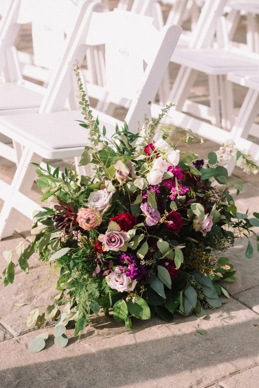 Whimsical, fall, autumn, jewel tones, gardeny, greenery, purples, blues, organic, wedding, arbor, aisle decor, aisle arrangements.
