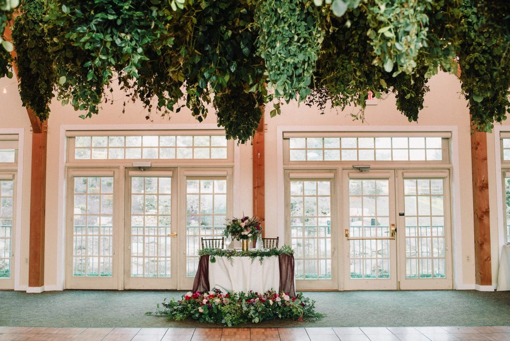 Whimsical, fall, autumn, jewel tones, gardeny, greenery, purples, blues, organic, wedding, greenery chandeliers, sweetheart table.