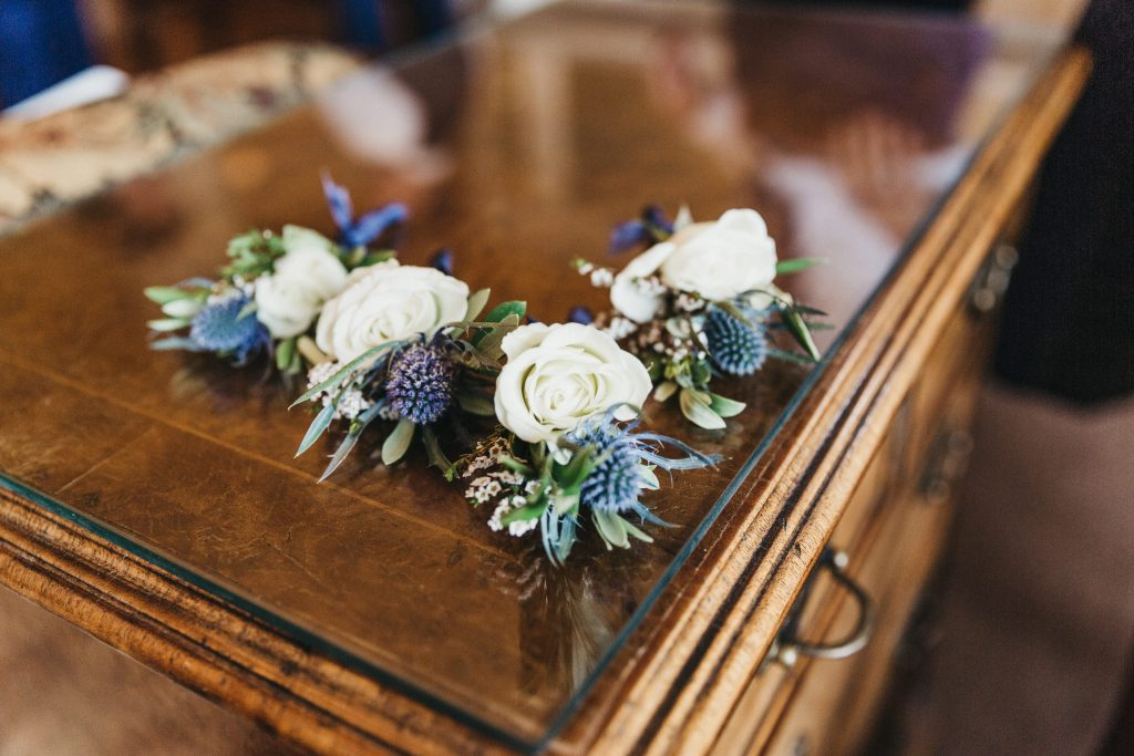 Summer wedding, warm, historic, personal, polished, clean, shades of blue, white, cream, roses, italian ruscus, blue thistle, boutonnieres.