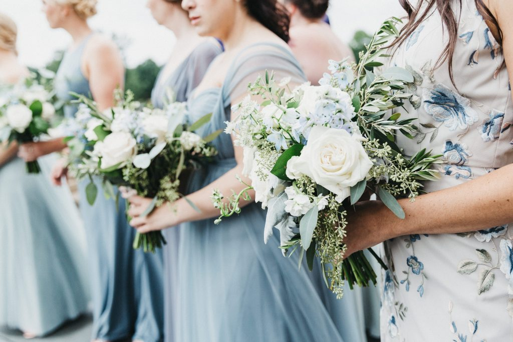 Summer wedding, warm, historic, personal, polished, clean, shades of blue, white, cream, roses, italian ruscus, blue thistle, bridesmaids bouquets, organic shape.