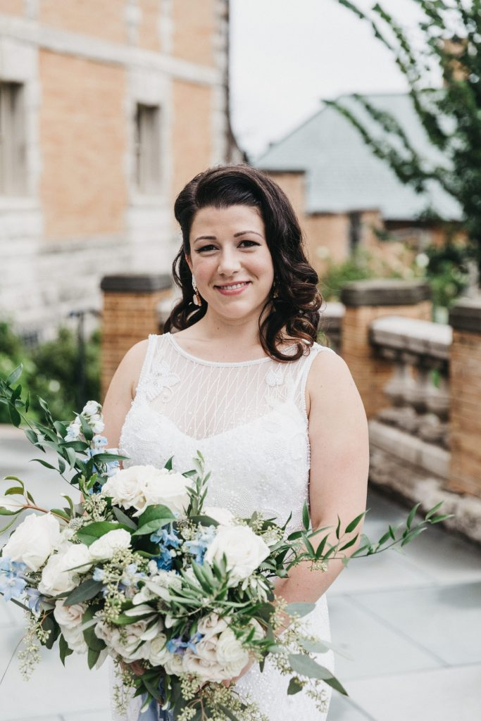 Summer wedding, warm, historic, personal, polished, clean, shades of blue, white, cream, roses, italian ruscus, blue thistle, bride and bridal bouquet, organic shape.