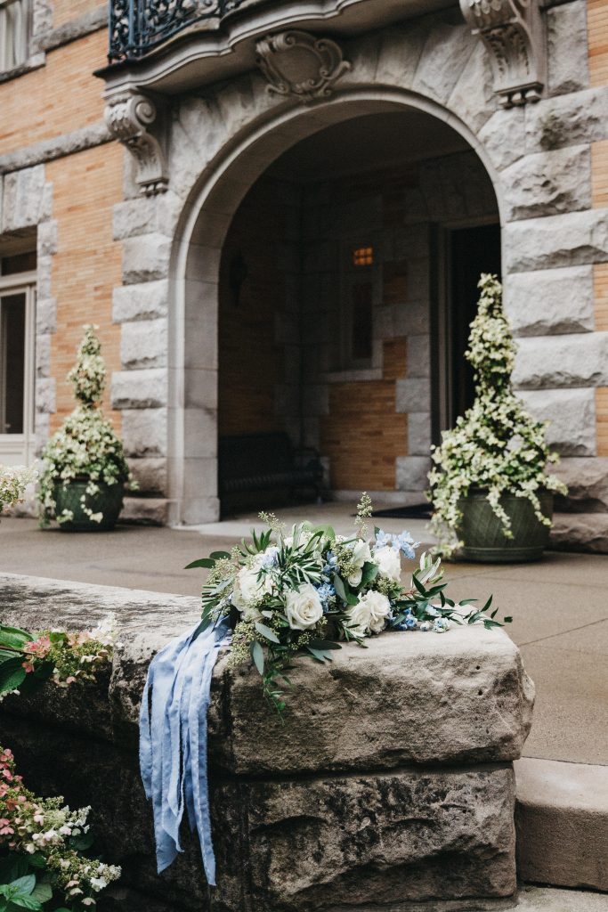 Summer wedding, warm, historic, personal, polished, clean, shades of blue, white, cream, roses, italian ruscus, blue thistle, bridal bouquet, stone building.