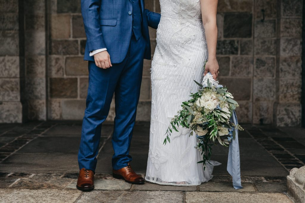 Summer wedding, warm, historic, personal, polished, clean, shades of blue, white, cream, roses, italian ruscus, blue thistle, bride and groom, stone building.
