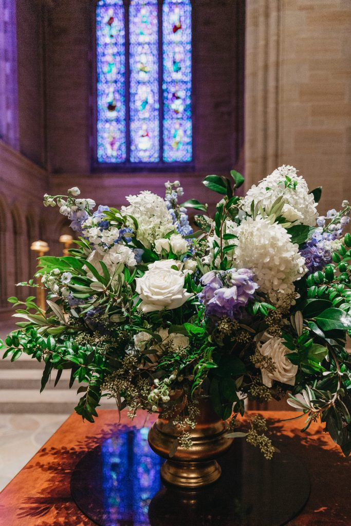 Summer wedding, warm, historic, personal, polished, clean, shades of blue, white, cream, roses, italian ruscus, blue thistle, altar arrangement.
