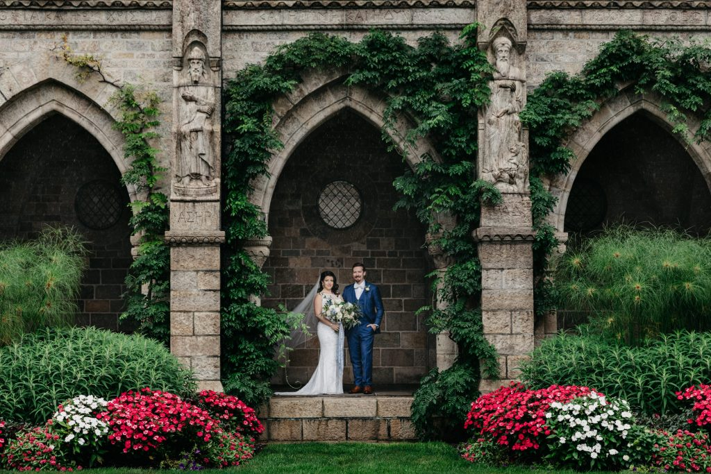 Summer wedding, warm, historic, personal, polished, clean, shades of blue, white, cream, roses, italian ruscus, blue thistle, bride and groom, stone building, ivy wall.