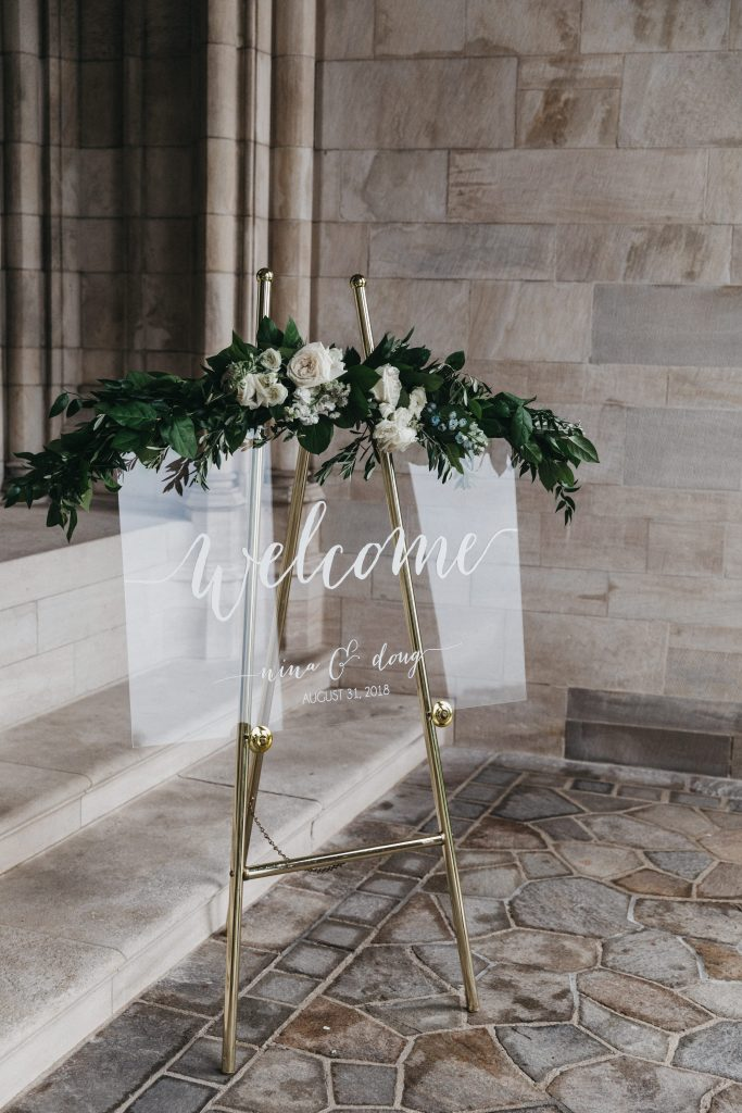 Summer wedding, warm, historic, personal, polished, clean, shades of blue, white, cream, roses, italian ruscus, blue thistle, welcome sign.