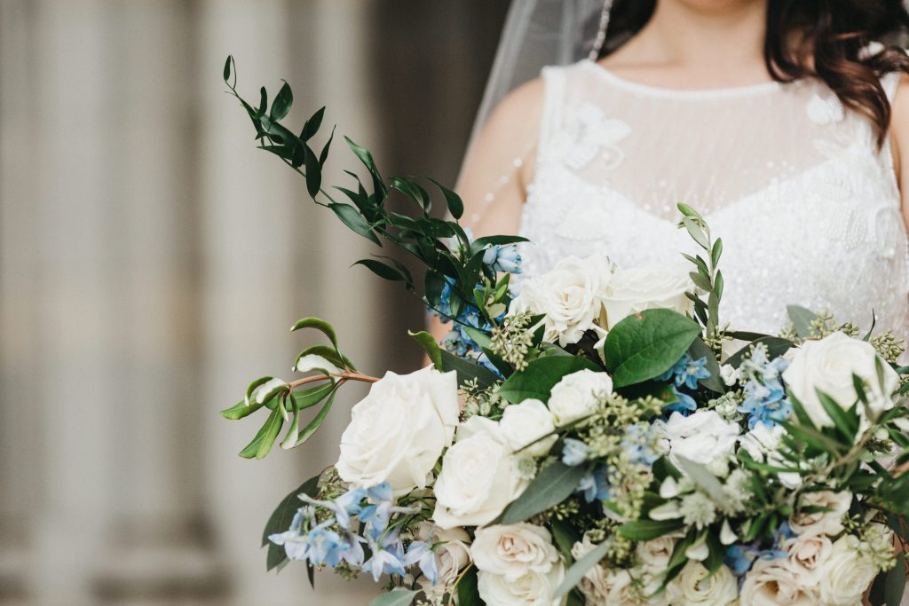 Summer wedding, warm, historic, personal, polished, clean, shades of blue, white, cream, roses, italian ruscus, blue thistle, bride and bridal bouquet.