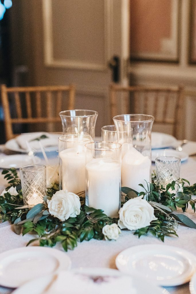 Summer wedding, warm, historic, personal, polished, clean, shades of blue, white, cream, roses, italian ruscus, blue thistle, reception, centerpiece, pillar candles, greenery.