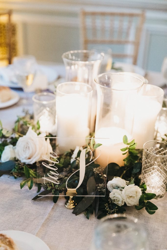 Summer wedding, warm, historic, personal, polished, clean, shades of blue, white, cream, roses, italian ruscus, blue thistle, reception, centerpieces, pillar candles, greenery.