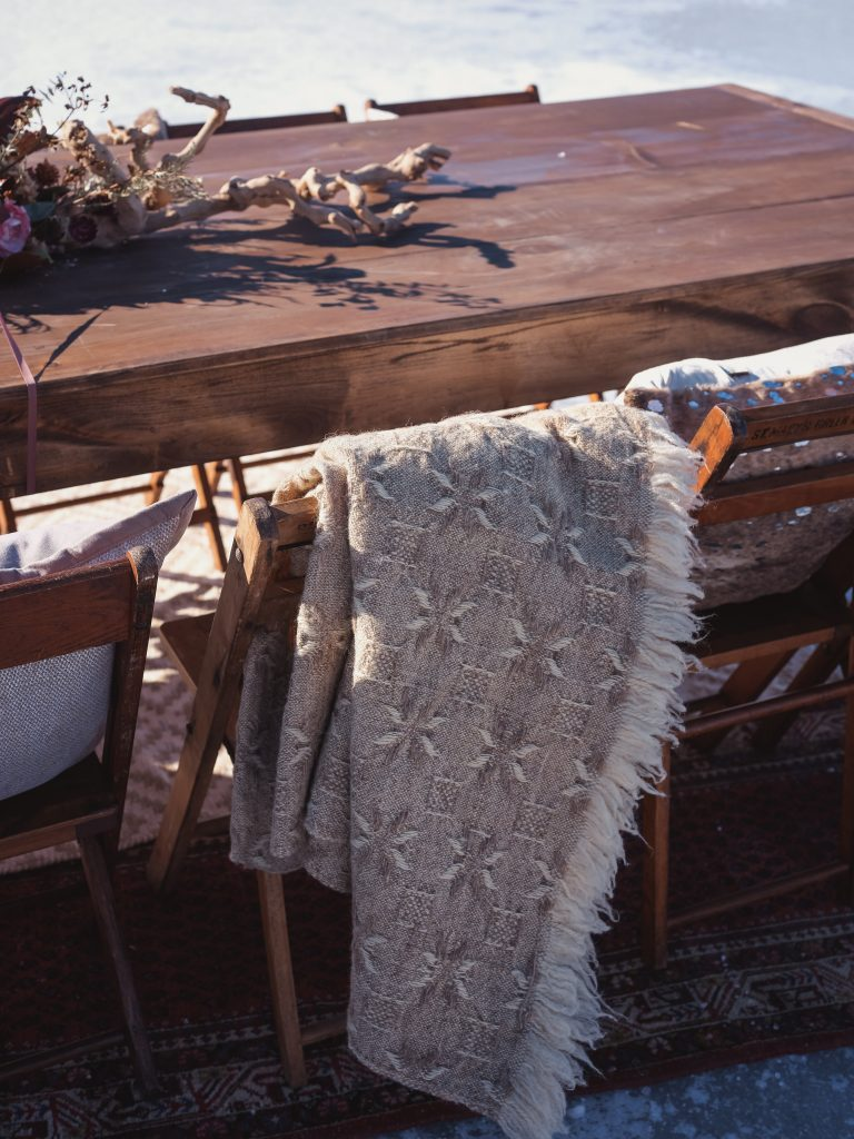 Ice wedding, ice dinner, tule bridal skirt, blush, burgundy, brown, dried florals, winter, frozen lake, styled shoot, table setting, blankets.