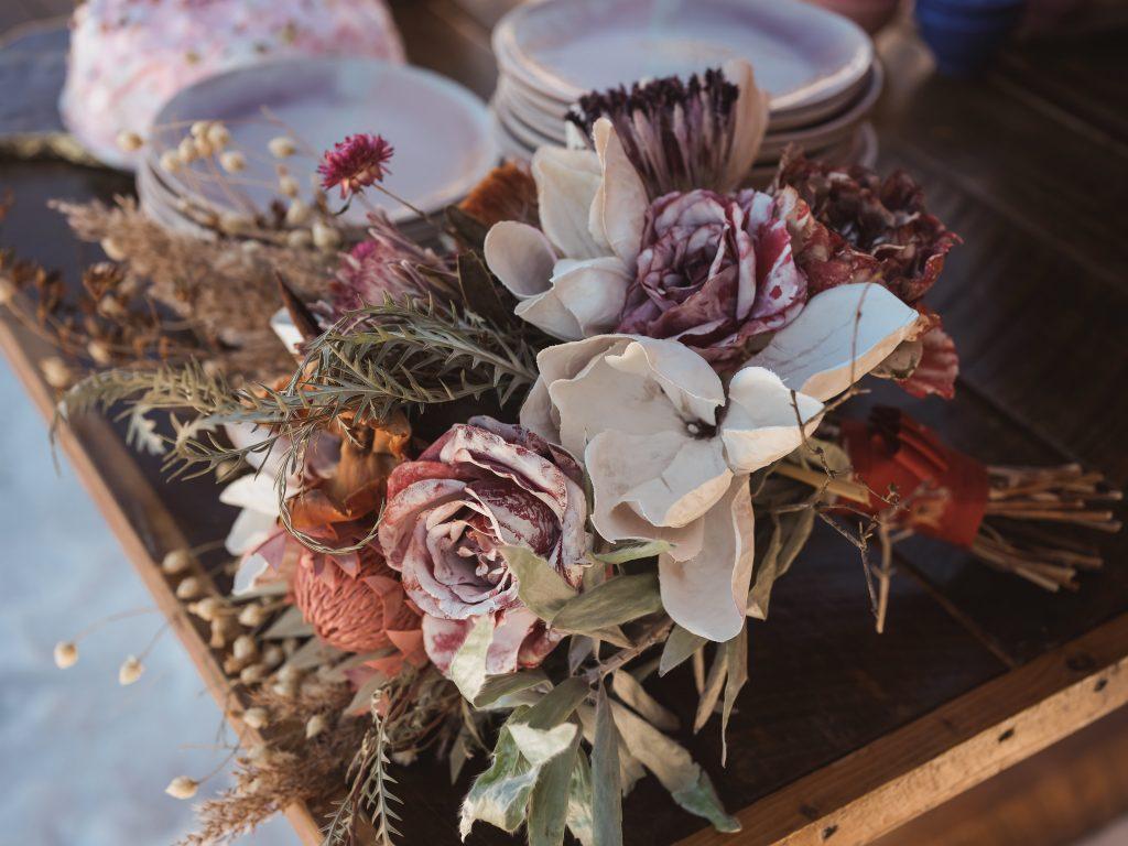 Ice wedding, ice dinner, tule bridal skirt, blush, burgundy, brown, dried florals, winter, frozen lake, styled shoot, bridal bouquet.