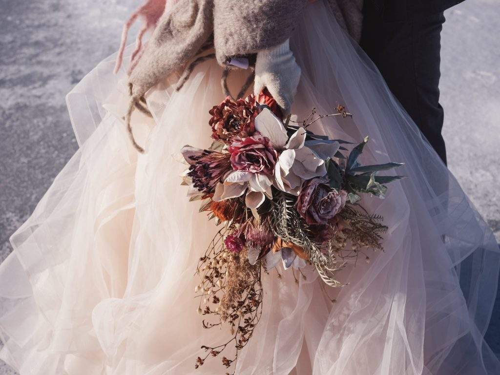 Ice wedding, ice dinner, tule bridal skirt, blush, burgundy, brown, dried florals, winter, frozen lake, styled shoot, bridal bouquet.