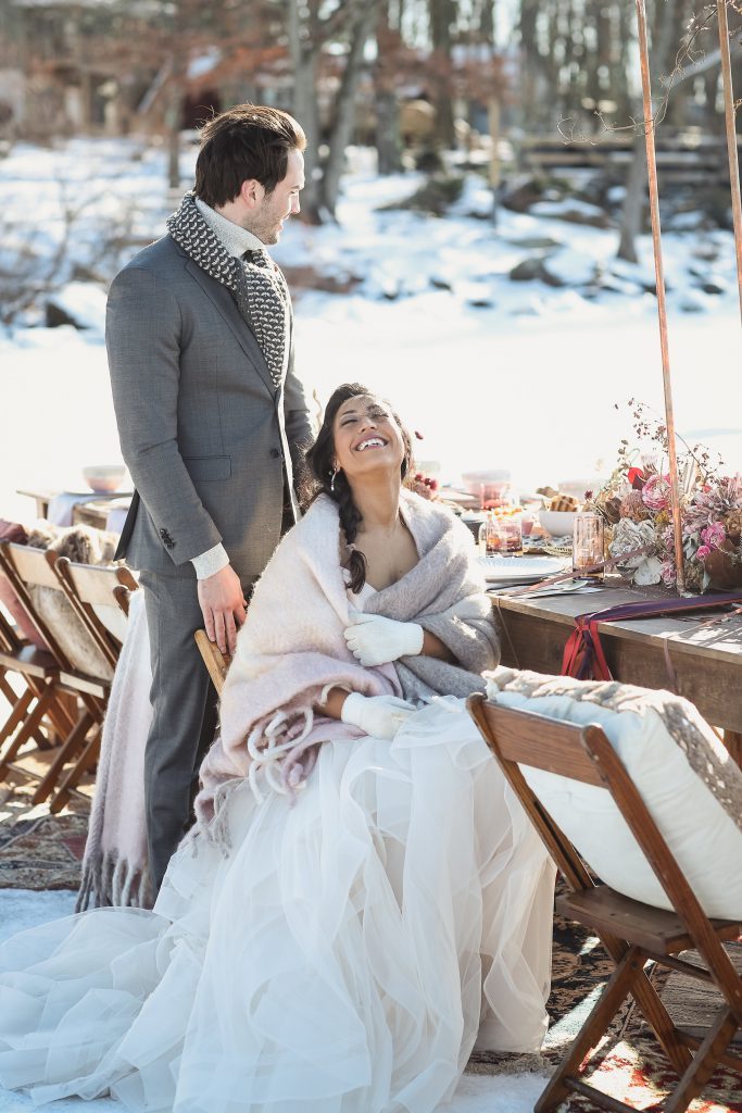 Ice wedding, ice dinner, tule bridal skirt, blush, burgundy, brown, dried florals, winter, frozen lake, styled shoot, dinner, table setting, blankets, ribbons, dried centerpiece, bride and groom.