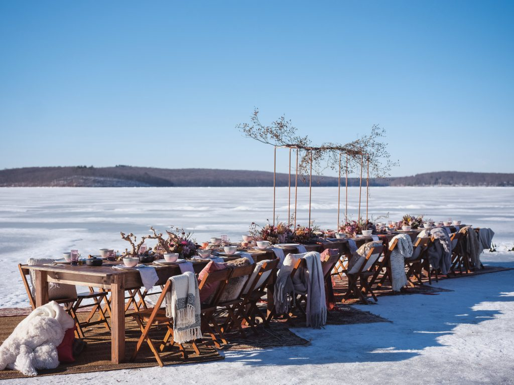 Ice wedding, ice dinner, tule bridal skirt, blush, burgundy, brown, dried florals, winter, frozen lake, styled shoot, dinner, table setting, blankets, ribbons, dried centerpiece.