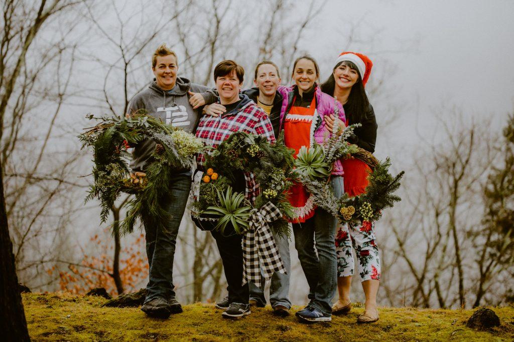 Holiday wreath making workshop, evergreens, mushrooms, oranges, airplants, pinecones, festive, gathering.