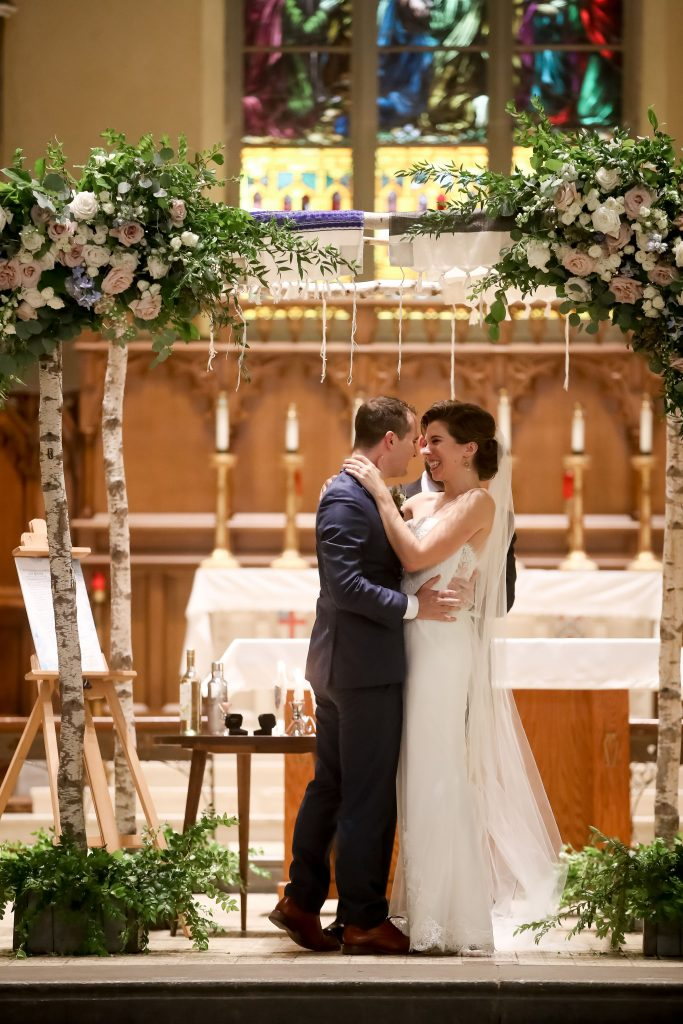 warm, loving, striking and fashionable, artistic, fall wedding, navy, slate bluish, pewter, blush, cream, greenery, texture, botanical, asymmetrical, ceremony, birch chuppah, floral corner pieces.